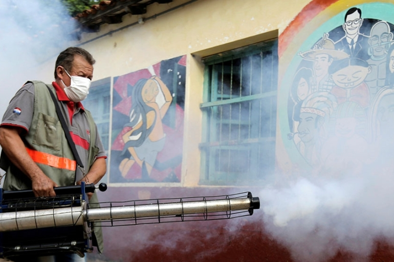 A Paraguayan federal health worker takes part in fumigation to prevent the proliferation of mosquitoes that transmit the dengue fever at the San Lorenzo National School, in a low-income neighbourhood of San Lorenzo, Paraguay [Jorge Adorno/Reuters]