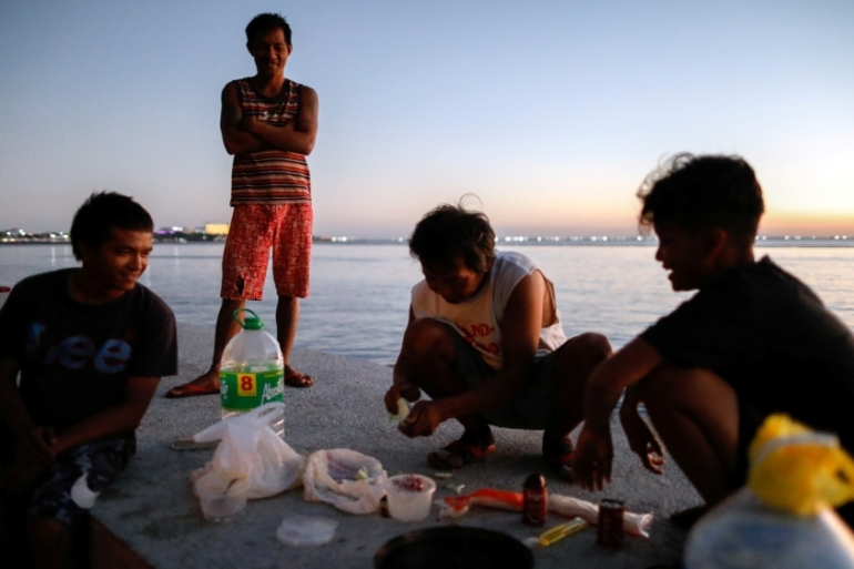 Some stranded and homeless Filipinos prepare dinner as they take shelter along Manila Bay following the announcement of a lockdown in Manila, the Philippines in April 2020 [File: Eloisa Lopez/Reuters]