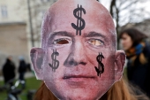 An activist holds up a mask depicting Amazon founder Jeff Bezos, during a protest against the opening of a new Amazon office in Berlin, Germany on February 22, 2020 [File: Reuters/Michele Tantussi]