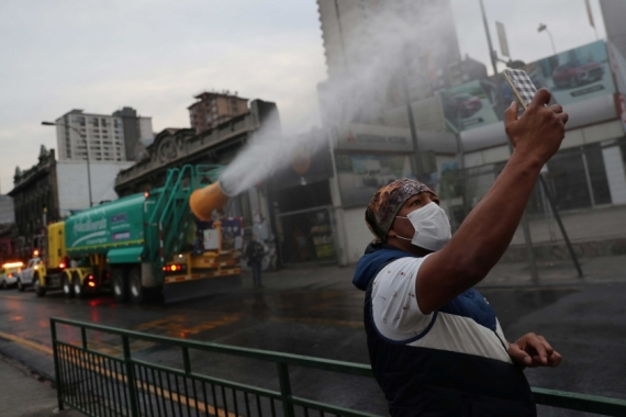A man takes a cellphone photo while a truck mix of quaternary ammonium compounds and water to disinfect streets in Santiago, Chile [Ivan Alvarado/Reuters]