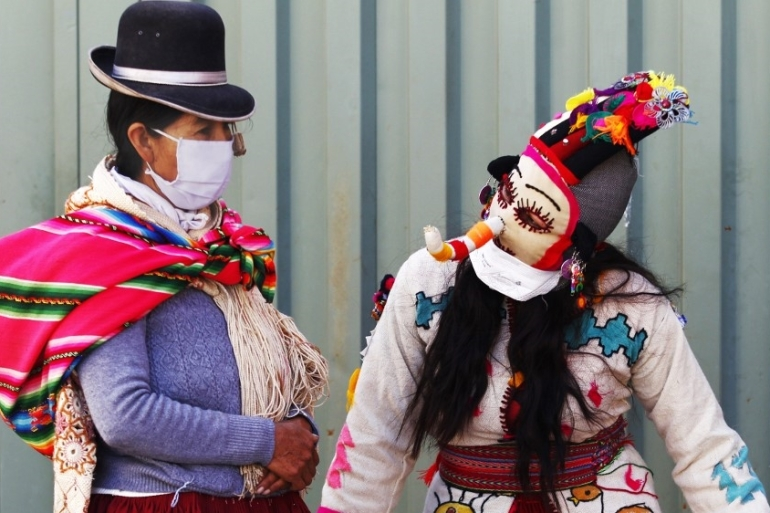 A person dressed as a Kusillo, a traditional Andean harlequin, reminds people to wear a face masks, gloves and maintain physical distance as a preventive measure against the novel coronavirus in Puno, Peru, on May 15, 2020 [Carlos Mamani/AFP]