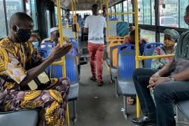 Passengers practice social distancing on a bus on the first day of the easing of lockdown measures in Lagos [Temilade Adelaja/Reuters]