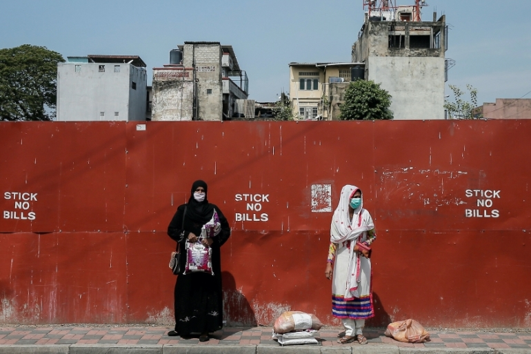 Two Muslim women wearing protective masks stand on a side of the main road, in Colombo, Sri Lanka April 1, 2020 [Dinuka Liyanawatte/Reuters]