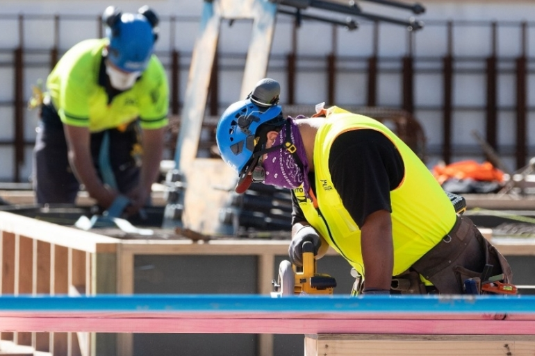 Masked construction workers are pictured at a building site on the first day of the easing of restrictions in Wellington on April 28, 2020, following the COVID-19 outbreak [Marty Melville/ AFP]