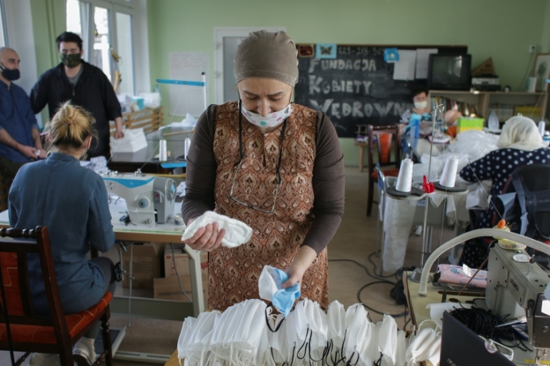 Chechen refugees prepare face masks to be distributed to first responders in Gdansk, Poland [Matej Leskovsek/Reuters]