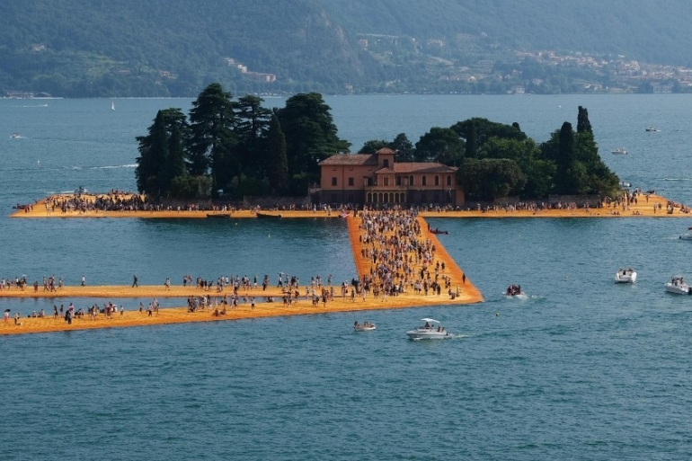 People walking the 'The Floating Piers' by Christo and Jeanne-Claude on Lake Iseo in July 2016. Christo has died aged 84 [Filippo Venezia/EPA]