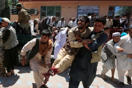 Men carry an injured person to a hospital in Jalalabad after a blast during a funeral ceremony in Nangarhar province [Parwiz/Reuters]