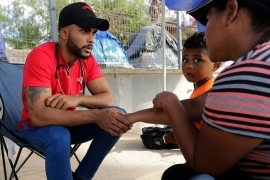 Rojas attends to fellow migrants at a sidewalk clinic in a refugee camp in Matamoros, Mexico [File: Eric Gay/AP Photo]