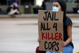A protester holds her sign at the Hennepin County Government Center as protests continue over the death of George Floyd [Jim Mone/AP Photo]