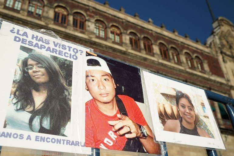 A banner of those disappeared hangs outside the National Palace in Mexico City where families are demanding the government take the search for their loved ones seriously [Eoin Wilson/Al Jazeera]
