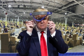 Trump holds up a protective face shield during a behind-the-scenes tour of a Ford facility in Michigan in May [File: Leah Millis/Reuters]