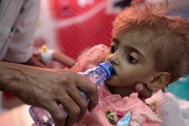 A father gives water to his malnourished daughter at a therapeutic centre in a hospital in Hodeidah, Yemen [File: Hani Mohammed/AP]