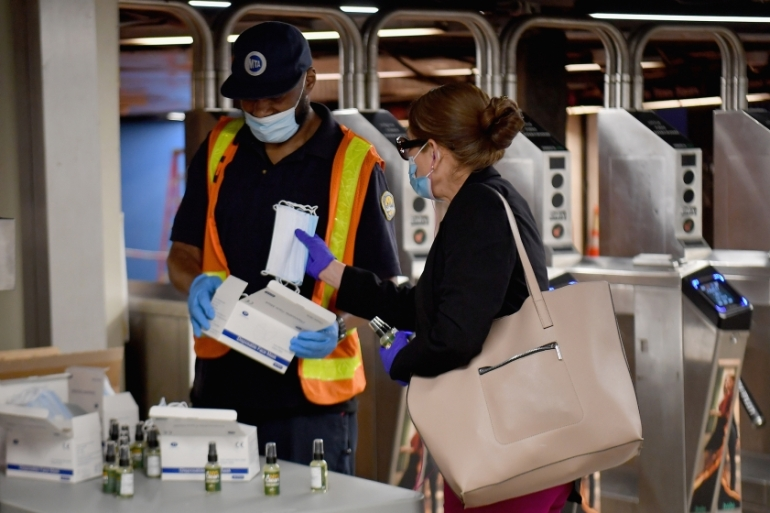 A transit worker hands out free hand sanitiser and face masks at Grand Central Station in New York City, where masks are required for anyone in public over the age of two who is not able to practice social distancing [File: Angela Weiss /AFP]