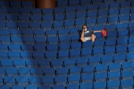 A Trump supporter in the sparsely filled upper decks of the arena as the president addresses his first re-election campaign rally in several months [Leah Millis/Reuters]