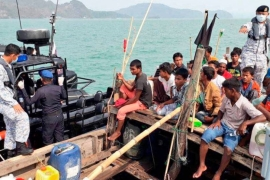 Malaysian navy officers detain a boat which carried Rohingya migrants off the island of Langkawi in 2018 [Royal Malaysian Navy via AP]