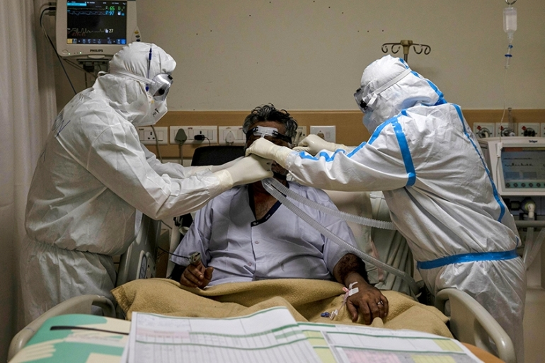 Medical workers wearing personal protective equipment tend to a coronavirus patient in the intensive care unit of a private hospital in New Delhi, India [File: Danish Siddiqui/Reuters]