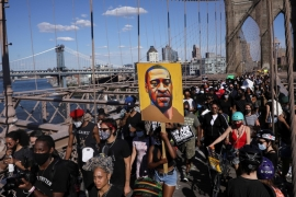 People hold signs on Brooklyn Bridge during a protest against police brutality and racism in the aftermath of the death of George Floyd in New York, US, on June 13, 2020 [Caitlin Ochs/Reuters]