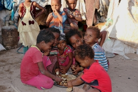 Children eat bread at a camp sheltering displaced people from the port city of Hodeidah near Aden, Yemen [File: Fawaz Salman/Reuters]