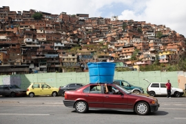 A car drives past hauling a plastic water tank on its rooftop, in the Petare neighbourhood of Caracas, Venezuela. [Ariana Cubillos/AP Photo]