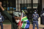 A woman holds a South African national flag during a protest against racism in front of the US Embassy in Pretoria, South Africa on June 5, 2020 [AP/Themba Hadebe]