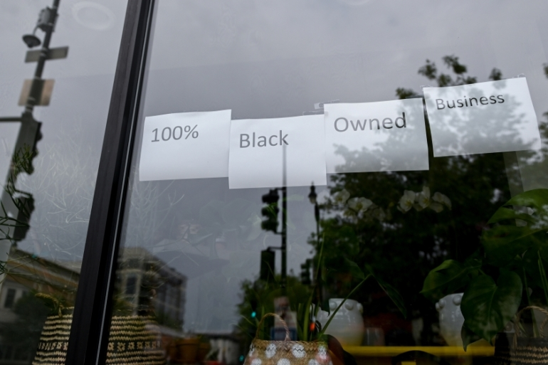Lee's Flower Shop, one of the oldest businesses in DC's U Street neighbourhood, posts signs on its windows before another night of protests against George Floyd's death in Minneapolis police custody, in Washington, DC, United States [File: Erin Scott/Reuters]