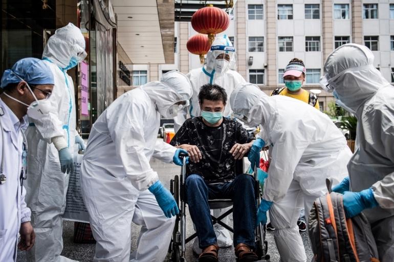 Petugas medis menggendong seorang pria yang merupakan pasien terakhir yang sembuh dari infeksi virus corona COVID-19 di Rumah Sakit Paru Wuhan [File: AFP]