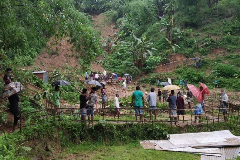 People gather at the site of a landslide in Udarband village, Cachar district in the Barak Valley of southern Assam state after three days of incessant pre-monsoon rains [AFP]