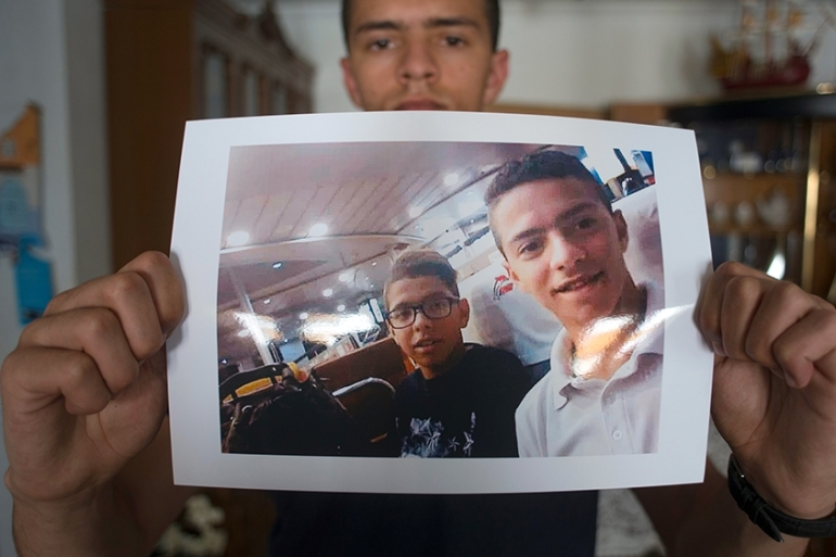 Anass al-Taheri, 22, holds a picture of himself and his brother Ilyass at his home in San Roque, Spain [Jorge Guerrero/AFP]
