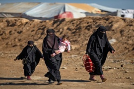 Women and children walk by Kurdish-run al-Hol camp for displaced Syrians in this January 14, 2020 photo [File: Delil Souleiman/AFP]