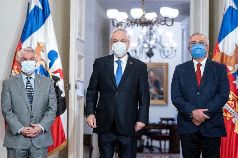 Chile President Sebastian Pinera, new Health Minister Oscar Enrique Paris and former Health Minister Jaime Manalich attend the cabinet reshuffle at the government house in Santiago, following the outbreak of COVID-19, in Santiago, Chile [Chile Presidency/Reuters]