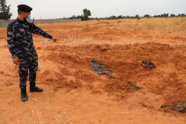 A member of security forces loyal to Libya's internationally recognised government points to a mass grave [File: Ismail Zitouny/Reuters]