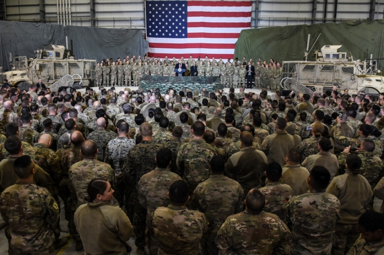 United States President Donald Trump speaks to the troops during a surprise visit to the Bagram base in Afghanistan last November. He has moved to impose sanctions on International Criminal Court employees over the court's investigation into alleged atrocities in the country [File: Olivier Douliery/AFP]
