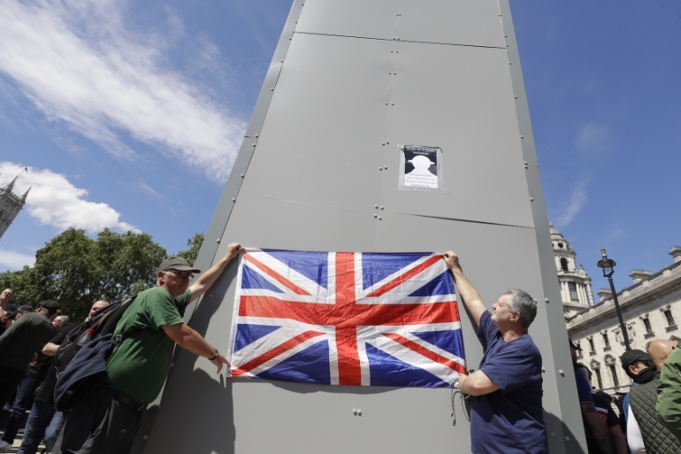 Members of far-right Football Lads Alliance hold a British flag in front of the covered statue of Winston Churchill in Parliament Square, London, June 13, 2020 [AP Photo/Kirsty Wigglesworth]