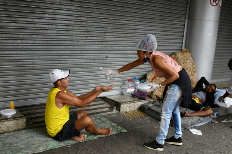 A member of a group of residents of the Chapeu Mangueira slum, sprays alcohol on the hand of a homeless person as she delivers him food during the coronavirus disease (COVID-19) outbreak, at Copacabana beach in Rio de Janeiro, Brazil, April 11, 2020 [Lucas Landau/Reuters]