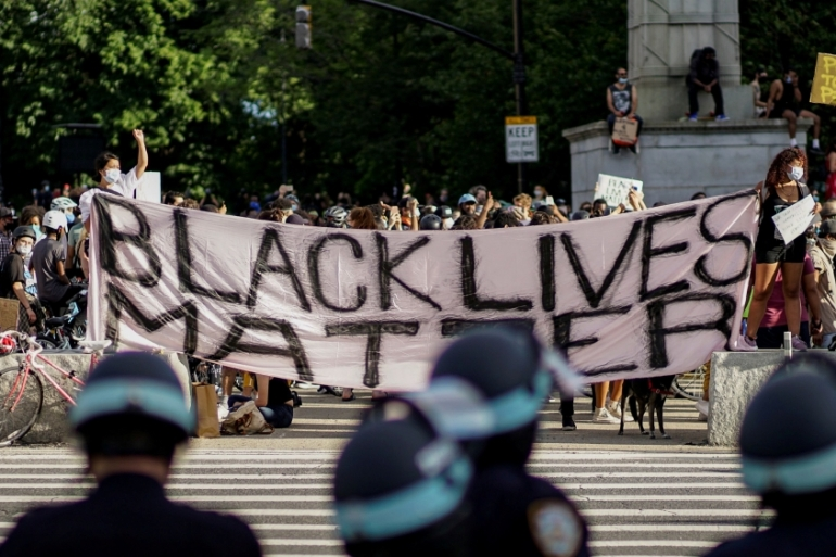 Demonstrators hold a Black Lives Matter banner during a protest against racial inequality [Reuters]