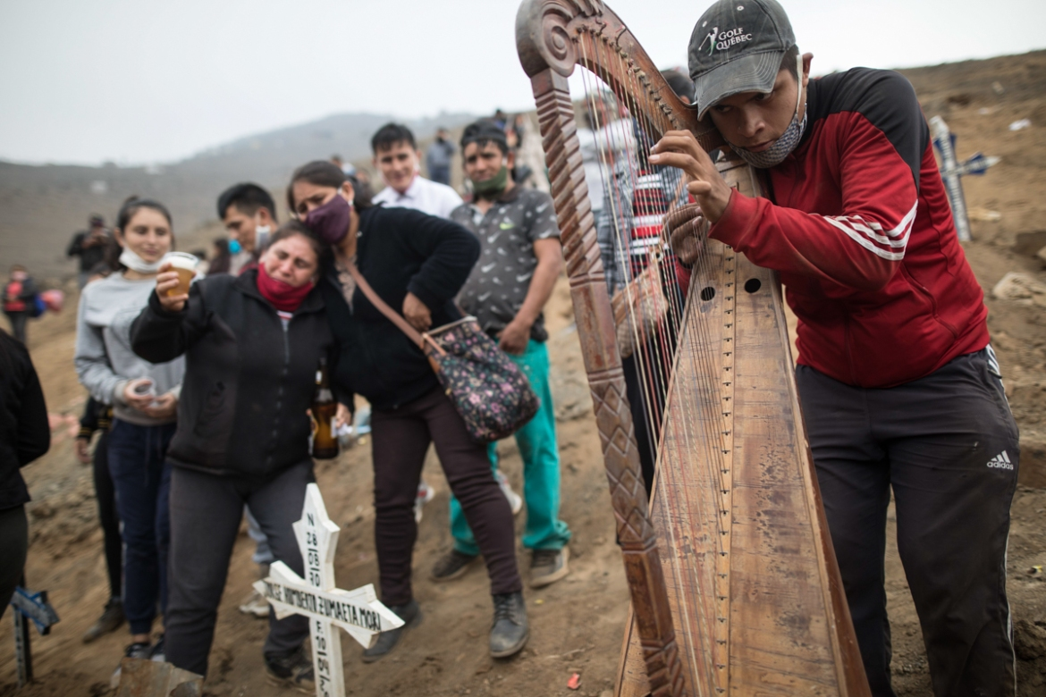 Harpist and cemetery worker Charlie Juarez plays music as Gregoria Zumaeta, left, mourns the death of her brothers Jorge Zumaeta, 50, and Miguel Zumaeta, 54, who died of COVID-19. [Rodrigo Abd/AP Photo]