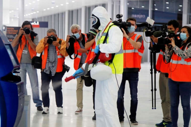 A worker in protective gear, surrounded by members of the media, sprays disinfectant at Paris Orly Airport in France, on June 26, 2020 [Charles Platiau/ Reuters]