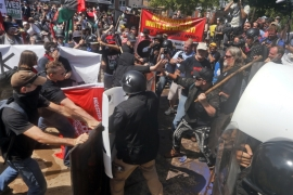 In this August 12, 2017 file photo, white nationalist demonstrators clash with counter demonstrators at the entrance to Lee Park in Charlottesville, Va, US [Steve Helber/AP Photo]