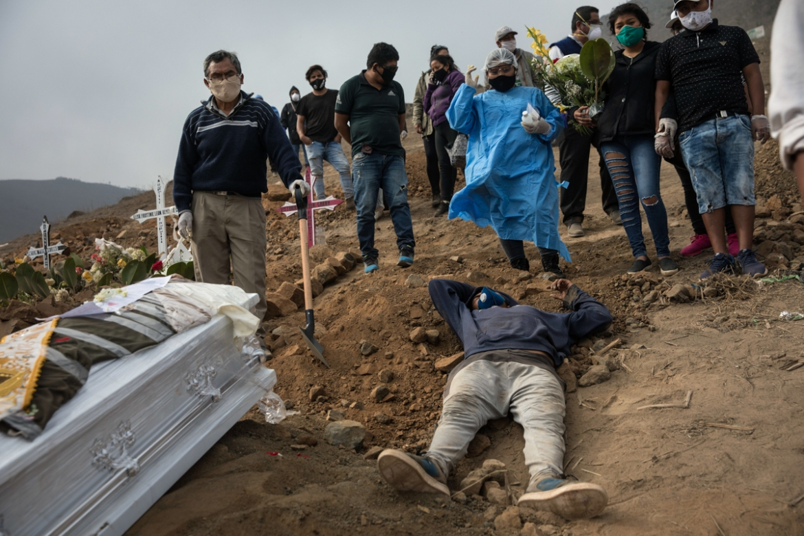 An exhausted cemetery worker lies on the ground after carrying the coffin of Victor Gaspar up the hill at the Nueva Esperanza cemetery. [Rodrigo Abd/AP Photo]