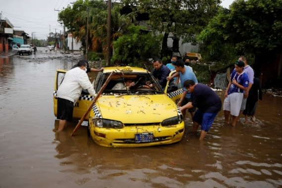 Neighbours try to move a taxi dragged by the water during floods caused by Tropical Storm Amanda at El Modelo neighborhood, in San Salvador [Jose Cabezas/Reuters]