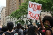 A protester carries a sign that reads 'Defund the police' on June 6, 2020, New York, US  [AP Photo/Ragan Clark]