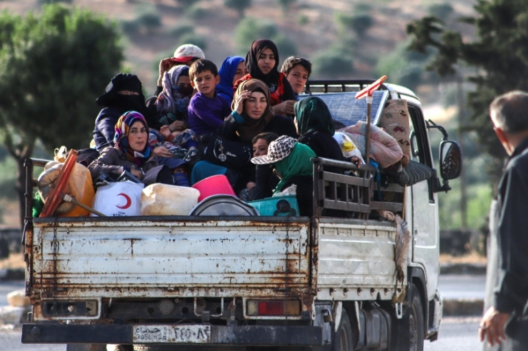 Displaced Syrians sit in the back of a truck as they flee along the M4 highway in rebel-held Idlib [Abdulaziz Ketaz/AFP]