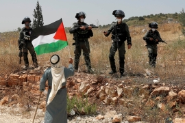 A demonstrator holds a Palestinian flag in front of Israeli forces during a protest against Israel's plan to annex parts of the illegally occupied West Bank, near Tulkarem [File: Mohamad Torokman/Reuters]