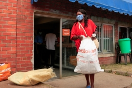 A woman collects groceries from a warehouse during the coronavirus lockdown in Harare, Zimbabwe, where many fear the country is returning to the 2008 era when a bout of hyperinflation rendered salaries worthless [File: Philimon Bulawayo/Reuters]