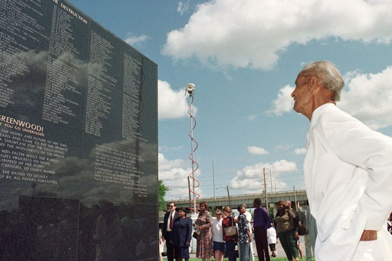 Tulsa race riot survivor George Monroe, now 82 years old, examines a monument dedicated in 1996 as part of the 75th-anniversary commemoration ceremonies in Tulsa, Oklahoma [File: Michael Wyke/AP Photo]