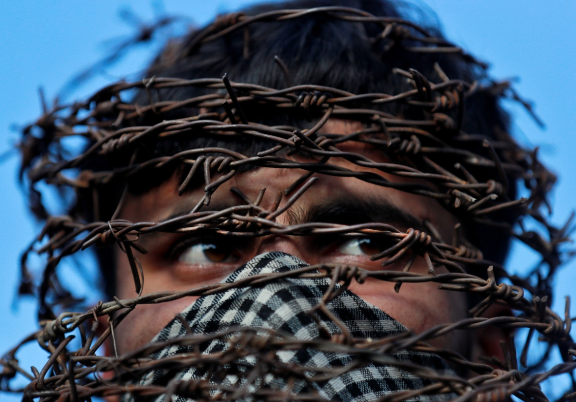 A masked Kashmiri man with his head covered with barbed wire attends a protest after Friday prayers in Srinagar on October 11, 2019. [Danish Ismail/Reuters]