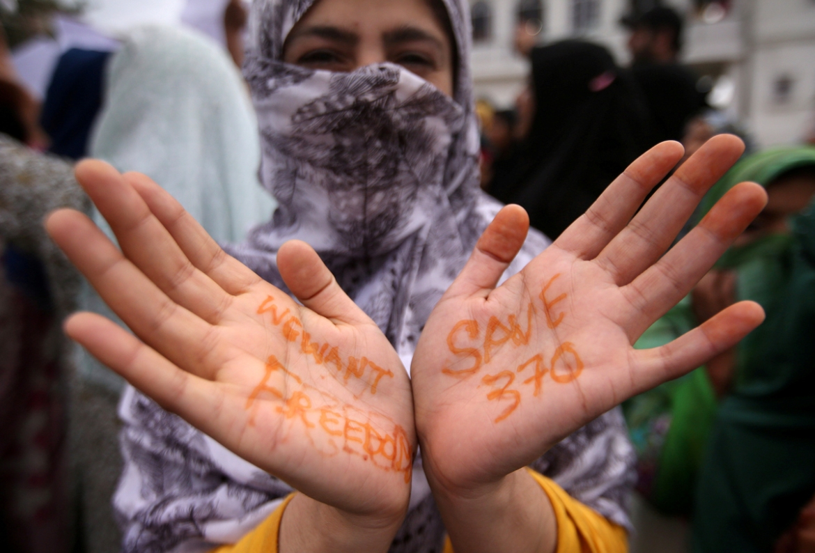 A Kashmiri woman shows her hands with messages at a protest after Friday prayers in Srinagar August 16, 2019. [Danish Ismail/Reuters]
