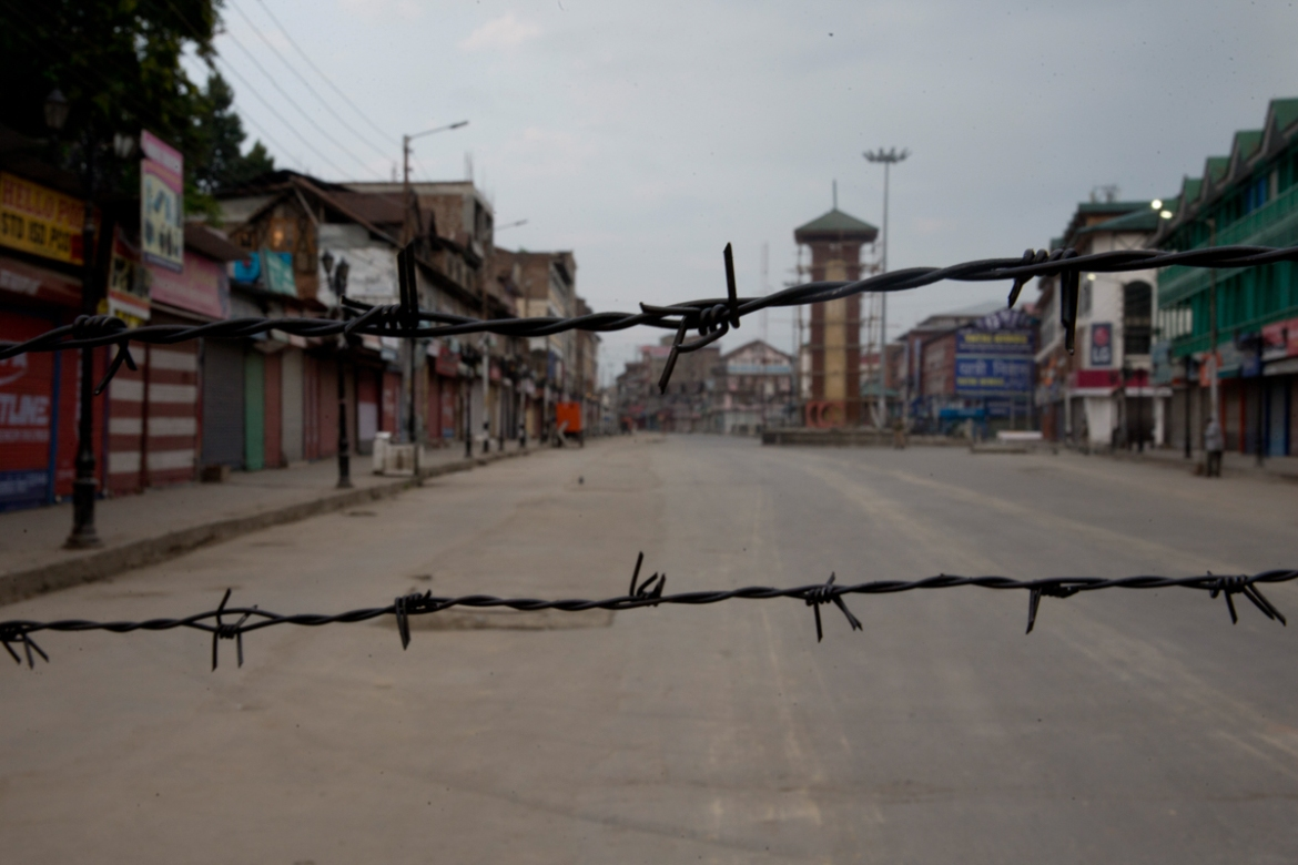 A deserted street is seen through a barbwire set up as a blockade during curfew in Srinagar on August 7, 2019. Authorities imposed a two-day curfew in Srinagar this week, citing intelligence tip-offs about possible protests. [Dar Yasin/AP Photo]
