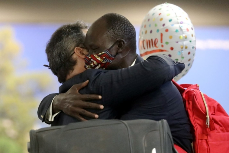 Peter Biar Ajak, right, embraces human rights lawyer Jared Genser after entering the International Arrivals area in Dulles International Airport [Leah Millis/Reuters]