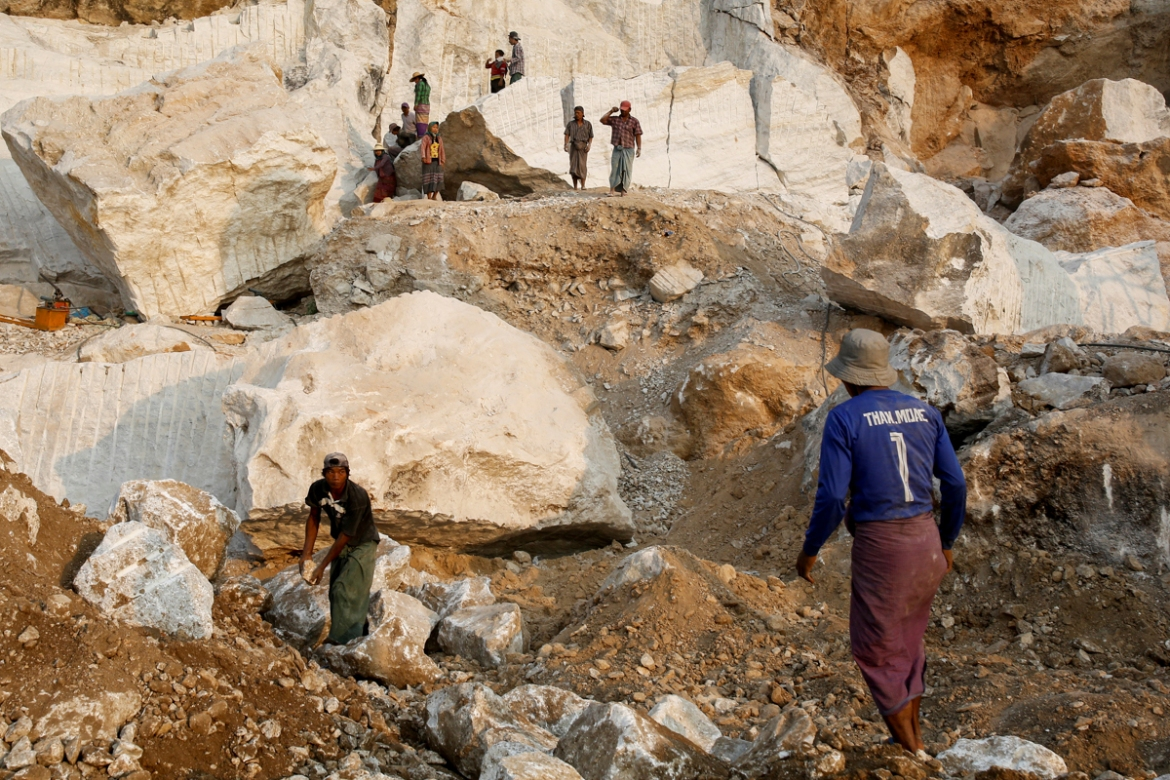 Workers at a marble site move pieces of extracted marble from a marble mine. [Ann Wang/Reuters]